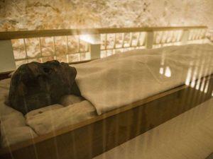 Mumie krále Tutanchamona zabalená do lněného plátna vystavená v klimatizované skleněné vitríně v jeho podzemní hrobce, Údolí králů. Autor: AFP