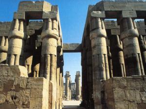 Svazčité sloupy s uzavřenou hlavicí na nádvoří Amenhotepa III. V pozadí je vidět kolonáda.
