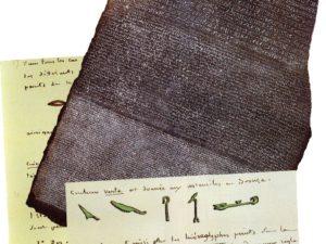 Rosettská deska objevená v roce 1799 a Champollionovy sešity s přepisy hieroglyfů.