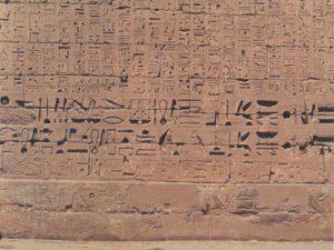 Stěna chrámu v Medinit Hábu na západním břehu Nilu v Thébách (Vasetu) pokrytá hieroglyfickým nápisem.