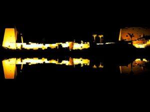 Amonův chrám v noci - zrcadlení ve Svatém jezeře. Chrámový komplex v Karnaku (Ipetisut) byl stále rozšiřován a s chrámem v nedalekém Luxoru (Ipetresejet) jej spojovala posvátná cesta, dromos. Při slavnostech opet se po ní vydávala na cestu posvátná Amonova bárka. Chrám navštěvoval bůh každoročně na dobu 11 dnů.