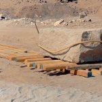 Přeprava obelisku po dřevěných kládách za pomocí válců.